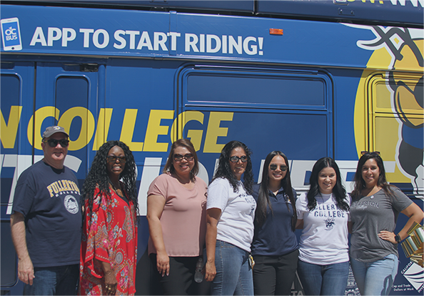 a group of college students standing in front of a bus