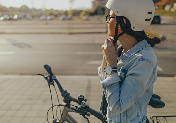 a woman on a bicycle clipping a helmet to her head