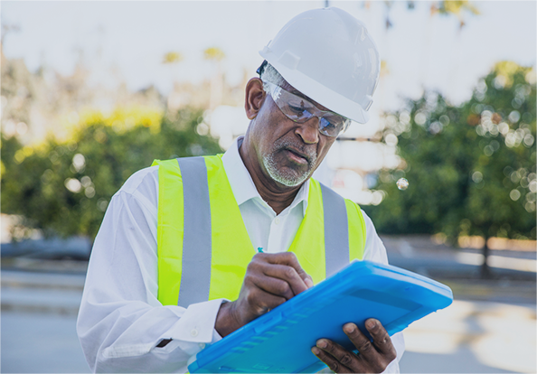a man with a hard hat and reflective vest on writing on a clipboard
